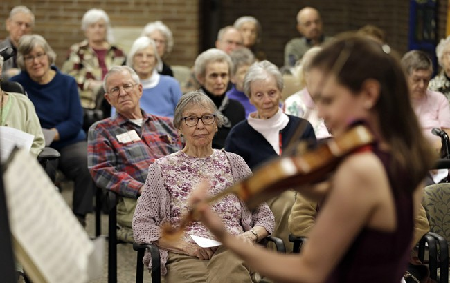 In this Thursday, Feb. 16, 2017 photo, residents watch Nina Sandberg play violin at Judson Park, in Cleveland Heights, Ohio.