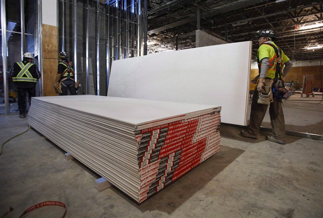 Construction workers move sheets of drywall at a building project in Calgary, Alta., on December 30, 2016.