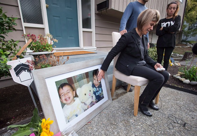 Tima Kurdi, touches a photo of her nephews Alan, left, and Ghalib Kurdi while speaking to the media outside her home in Coquitlam, B.C., on Thursday, Sept. 3, 2015.