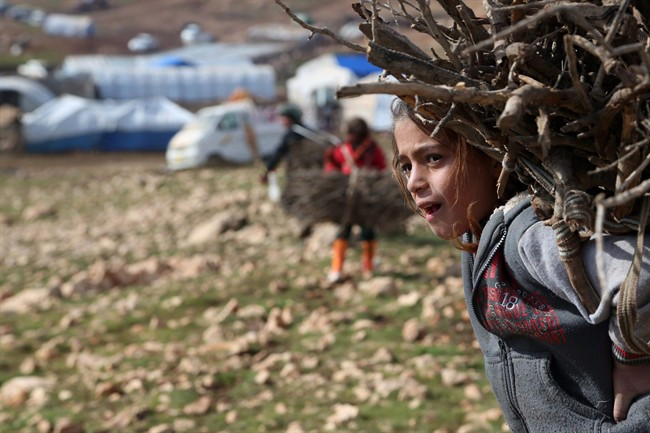 An Iraqi girl from the Yazidi minority carries firewood on Mount Sinjar in northern Iraq in a Monday, Jan. 12, 2015 file photo.
