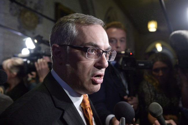 Tony Clement fields questions in the foyer outside the House of Commons in Ottawa, Monday, May 11, 2015.