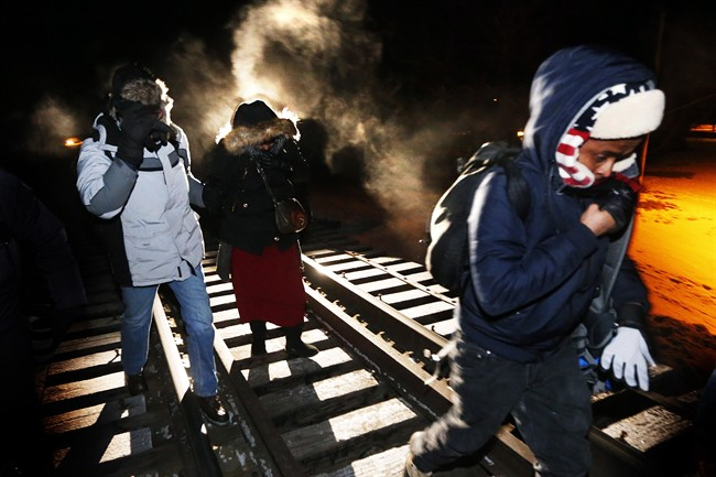 Asylum seekers from Somalia cross into Canada illegally from the United States by walking down a train track into the town of Emerson, Man., early Sunday morning, Feb.26, 2017.