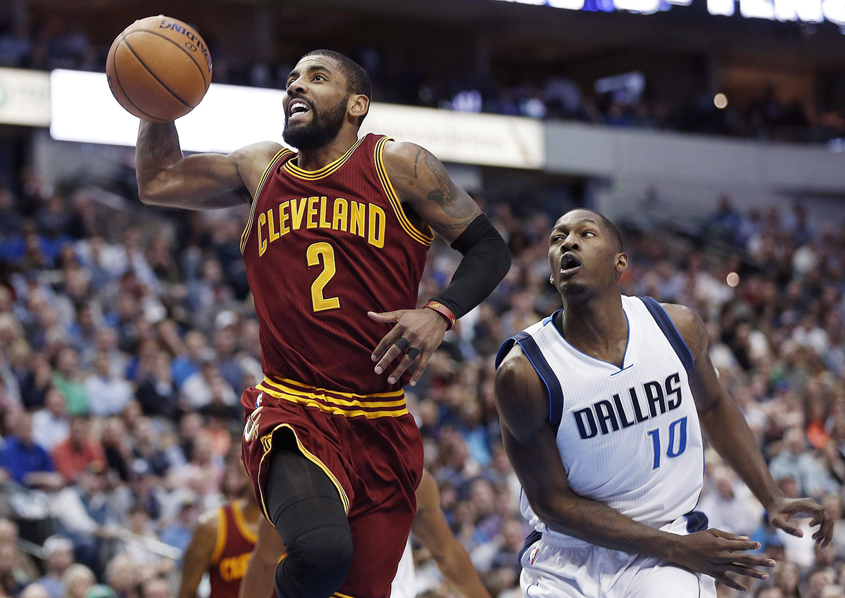 Cleveland Cavaliers guard Kyrie Irving (2) battles past Dallas Mavericks guard Yogi Ferrell (10) for a layup during the first half of an NBA basketball game, Monday, Jan. 30, 2017, in Dallas.