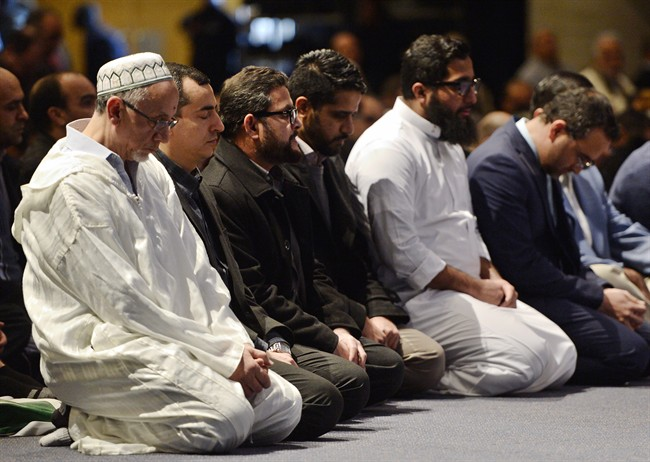 People pray at a funeral service for three of the six victims of the Quebec City mosque shooting at the Quebec City convention centre Friday, February 3, 2017.