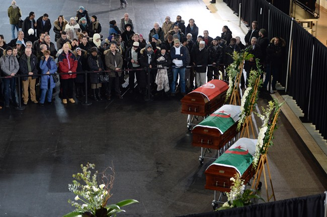 Mourners look on as the caskets of three of the victims of the Quebec City mosque shooting are lined up before a funeral at the Maurice Richard Arena in Montreal, Thursday, February 2, 2017.