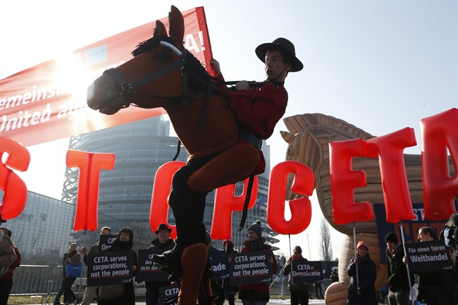 Activists stage a demonstration against CETA, the Canada-EU trade deal, outside the European Parliament in Strasbourg, eastern France, Wednesday, Feb. 15, 2017. Will extent to which the trade deal will help Canadians is yet to be seen.