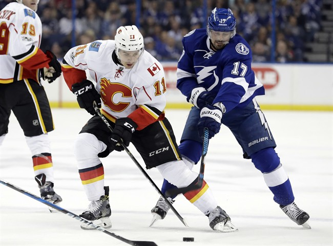 Calgary Flames center Mikael Backlund (11), of Sweden, gets hooked by Tampa Bay Lightning left wing Alex Killorn (17) during the first period of an NHL hockey game Thursday, Feb. 23, 2017, in Tampa, Fla.