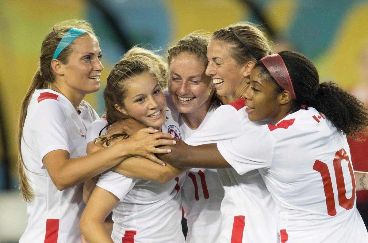 Shelina Zadorsky (left) congratulates Jessie Fleming and her Canadian teammates following a goal at the 2015 Pan Am Games.