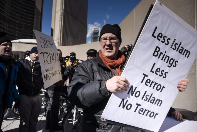 An anti-Islamic protester is pursued by a group of protesters with opposing views during a demonstration regarding motion M-103 at Toronto City Hall on Saturday, March 4, 2017.