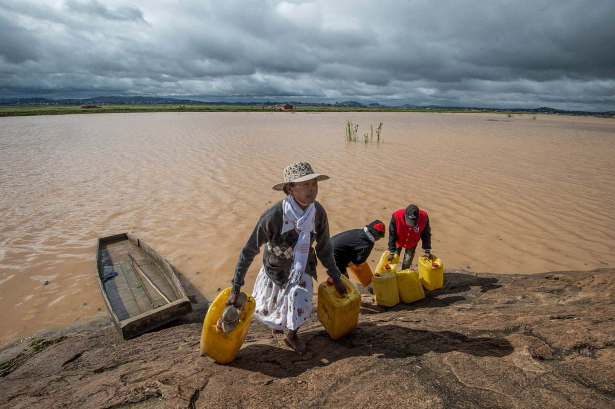 Residents cross flooded land and canal in Madagascar's capital Antananarivo, on Friday, March 10, 2017, to collect fresh water.  Cyclone Enawo hit land Tuesday, claiming the lives of at least five people and forcing some 10,000 people abandon their homes because of storm damage.