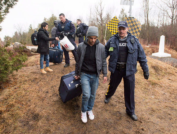 Asylum seekers, claiming to be from Yemen, are arrested by RCMP officers after crossing the border from New York into Canada on Wednesday, March 8, 2017 in Hemmingford, Quebec.