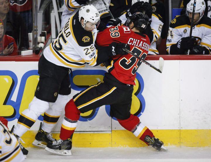 Boston Bruins' Brandon Carlo, left, checks Calgary Flames' Alex Chiasson during first period NHL hockey action in Calgary, Wednesday, March 15, 2017.
