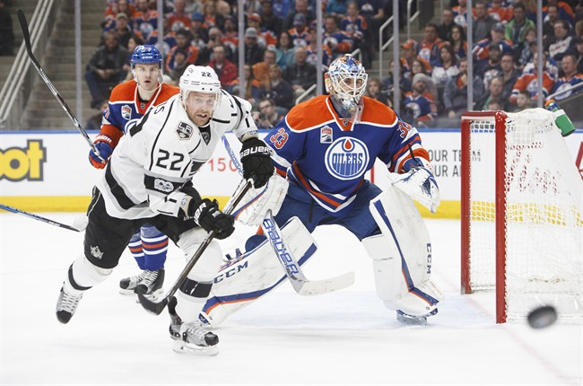 Edmonton Oilers' goaltender Cam Talbot (33) keeps his eye on the puck as Los Angeles Kings' Trevor Lewis (22) races for possession during third period NHL action in Edmonton, Alta., on Monday, March 20, 2017.