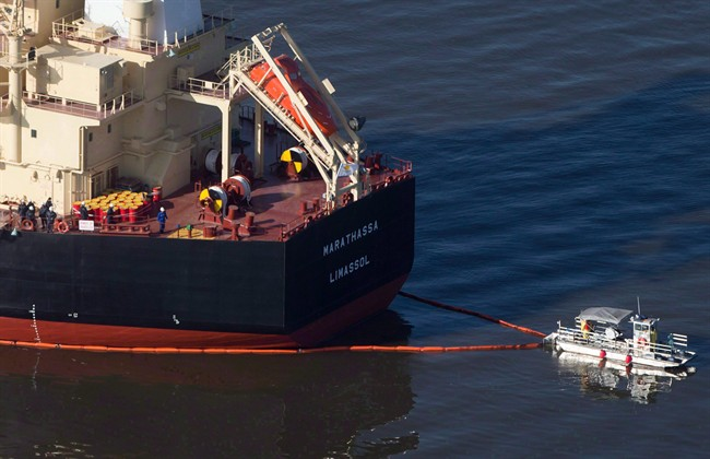 A spill response boat secures a boom around the bulk carrier cargo ship MV Marathassa after a bunker fuel spill in Vancouver, B.C., on April 9, 2015. Charges have been laid against the owners of the MV Marathassa nearly two years after a leak of bunker fuel onto the beaches of English Bay in Vancouver.