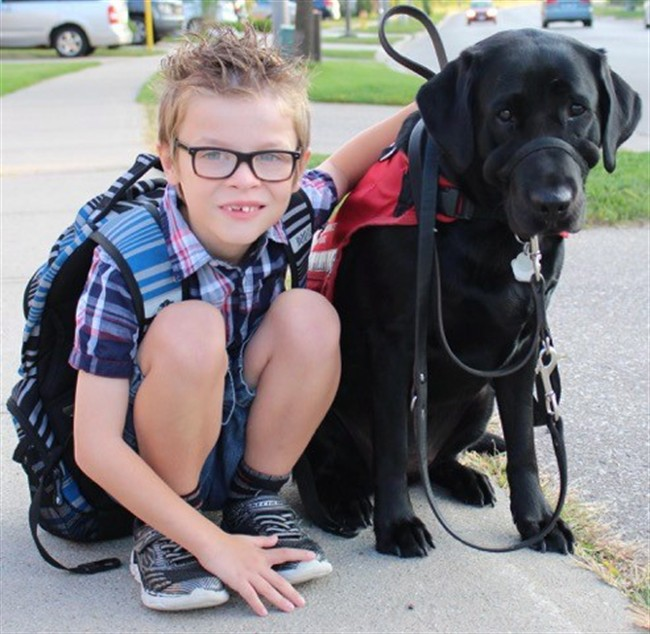 Kenner Fee poses for a photo with his service dog Ivy in this undated handout photo. An Ontario family has gone to the province's human rights tribunal to fight for their autistic son's right to bring his service animal into class.