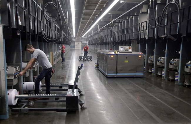 Workers and robots labour side-by-side with plastic thread made from recycled bottles at the Repreve Bottle Processing Center, part of the Unifi textile company in Yadkinville, N.C., in an October 21, 2016, file photo.