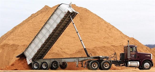A truck dumps a load of silica sand at Modern Transport Rail loading terminal in Winona, Minn., on Feb. 13, 2012.