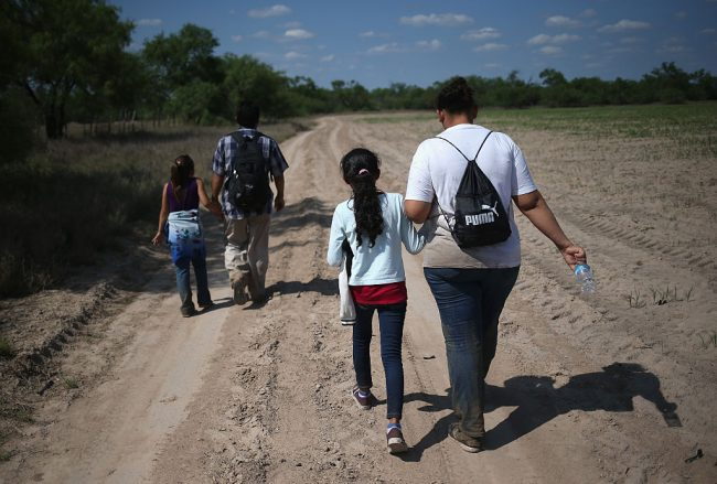 Central American immigrant families walk through the countryside after crossing from Mexico into the United States to seek asylum on April 14, 2016 in Roma, Texas.