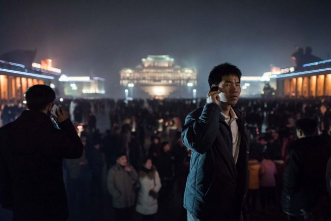 A man talks on a mobile phone after a fireworks display in front of Kim Il-Sung square, and next to an ice festival near the Taedong river, on the occasion of the 75th anniversary of the birth of Kim Jong-Il, in central Pyongyang on February 16, 2017.