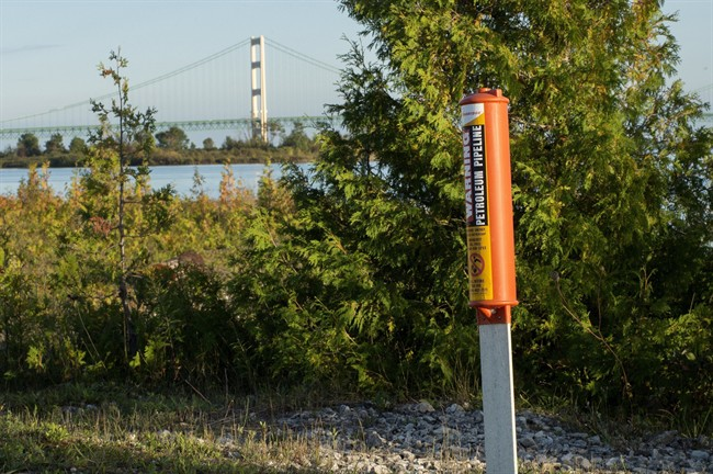In this Sept. 23, 2015, file photo, the Mackinac Bridge is visible from a marker near Enbridge Line 5 on the northern shore of the Straits of Mackinac in Michigan.