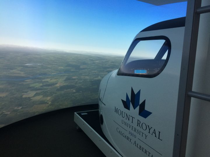 People attending the aviation career expo at Mount Royal University Saturday, March 11, 2017 use a flight simulator.