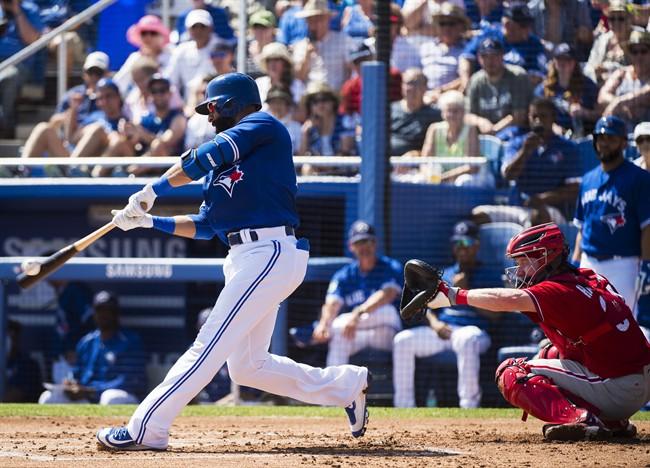 Toronto Blue Jays right fielder Jose Bautista (19) hits a single as Philadelphia Phillies catcher Ryan Hanigan (34) watches during first inning Grapefruit baseball spring training action in Dunedin, Fla., on Thursday, March 2, 2017.