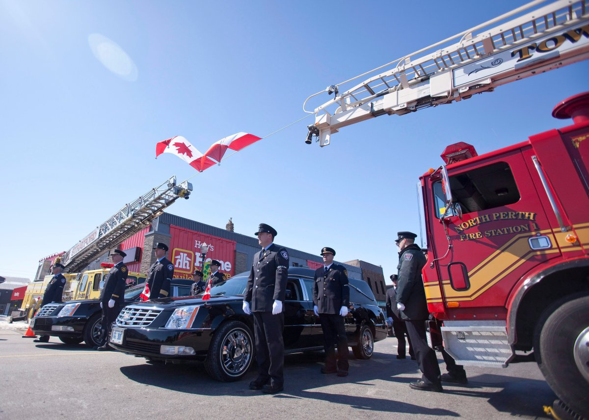 Firefighters escort hearses carrying their fallen colleagues Ken Rea and Ray Walter during a funeral procession in Listowel Ontario, March 24, 2011.