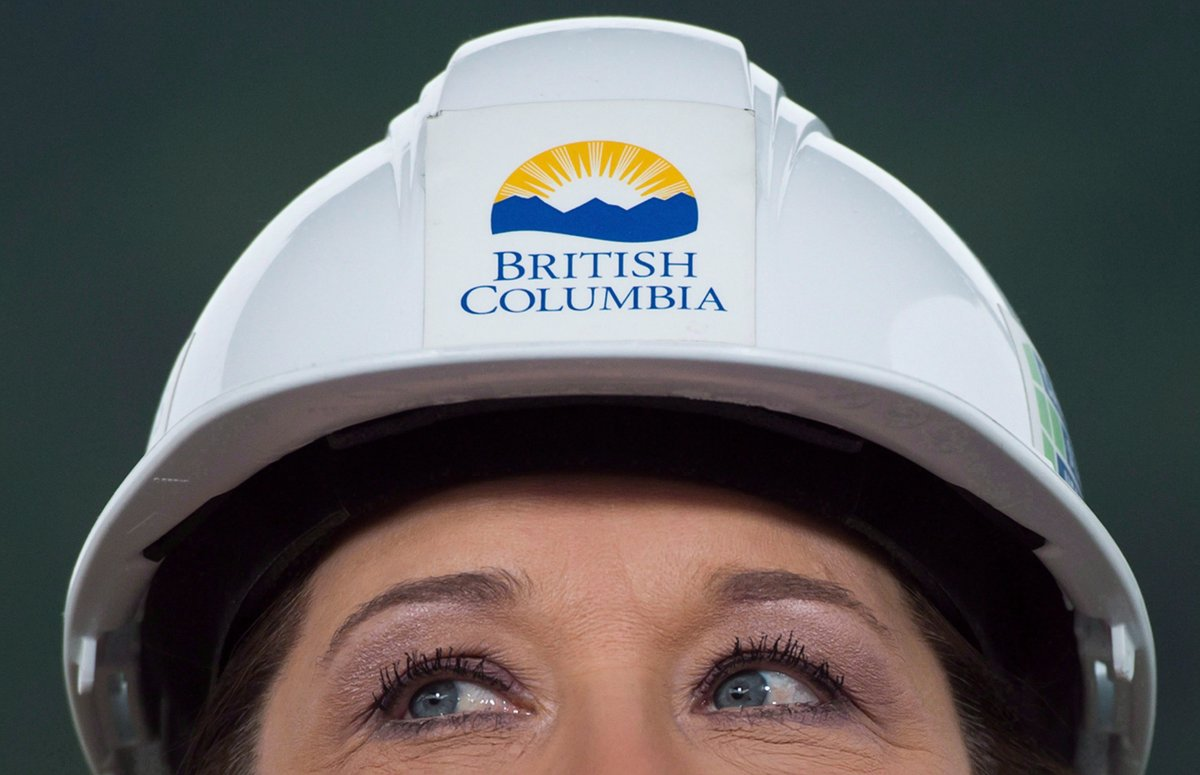 Wearing a hard hat, B.C. Premier Christy Clark listens to a question at the Woodfibre LNG project site near Squamish, B.C., on Friday November 4, 2016.