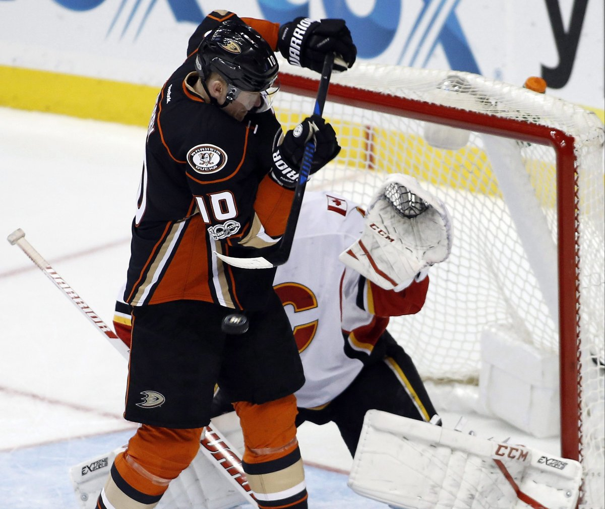 Anaheim Ducks right wing Corey Perry, left, redirects the puck against Calgary Flames goalie Brian Elliott (1) during the third period of an NHL hockey game in Anaheim, Calif., Tuesday, April 4, 2017. The Ducks won 3-1. (AP Photo/Alex Gallardo).