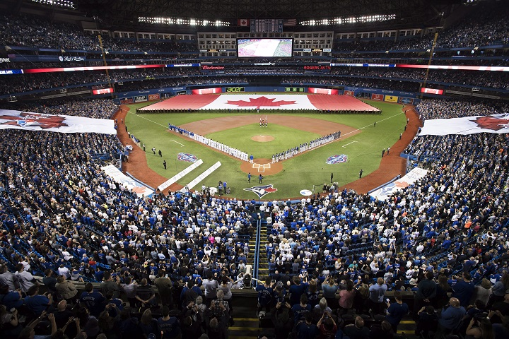 Toronto Blue Jays and Milwaukee Brewers players stand for the national anthems prior to interleague baseball action in Toronto, Tuesday, April 11, 2017.
