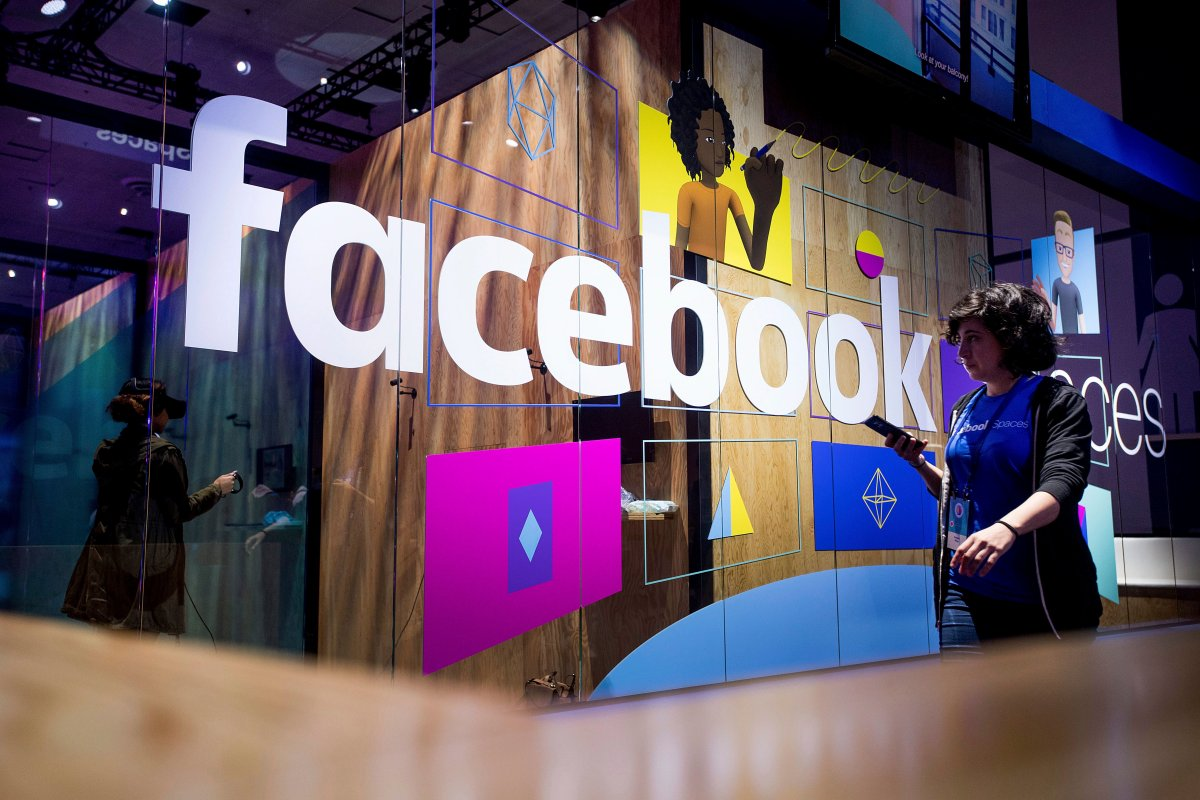 A conference worker passes a demo booth at Facebook's annual F8 developer conference, Tuesday, April 18, 2017, in San Jose, Calif.