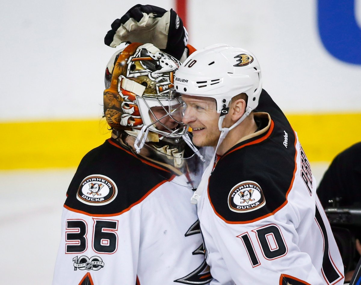 Anaheim Ducksgoalie John Gibson, left, celebrates with teammate Corey Perry after third period NHL hockey round one playoff action against the Calgary Flames, in Calgary, Wednesday, April 19, 2017.