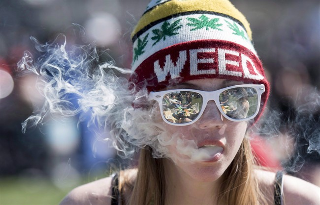A woman exhales while smoking a joint during the annual 420 marijuana rally on Parliament hill on Wednesday, April 20, 2016 in Ottawa.