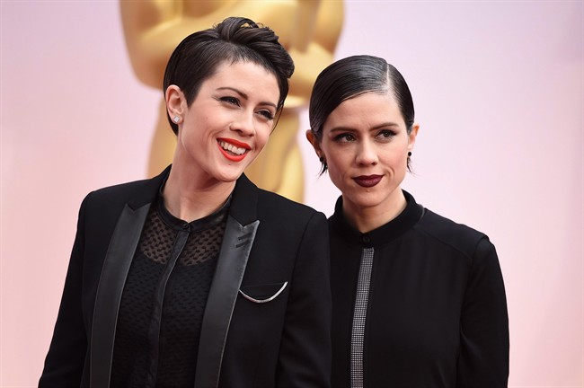 Tegan Quin, left, and Sara Quin of the musical group Tegan and Sara arrive at the Oscars on Sunday, Feb. 22, 2015, at the Dolby Theatre in Los Angeles. Twin sisters Tegan and Sara are putting their names behind social causes in a bigger way than ever this year.