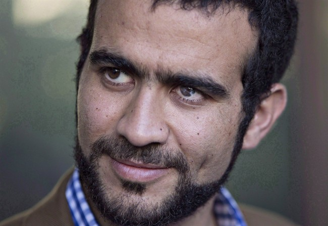 Omar Khadr watches as his lawyer Dennis Edney speaks to media after his bail conditions hearing in Edmonton on Friday, September 11, 2015. Khadr's official criminal record in Canada contains oddities and errors that are at odds with how the federal government viewed him on his return from the notorious prison on the U.S. naval base at Guantanamo Bay, Cuba.