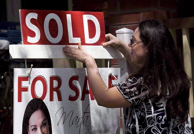 """A real estate agent puts up a """"sold"""" sign in front of a house in Toronto, Tuesday, April 20, 2010."""