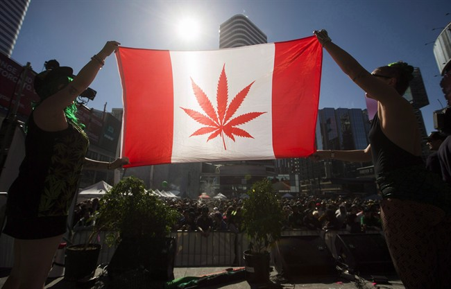 """Two people hold a modified design of the Canadian flag with a marijuana leaf in place of the maple leaf during the """"420 Toronto"""" rally in Toronto, April 20, 2016."""
