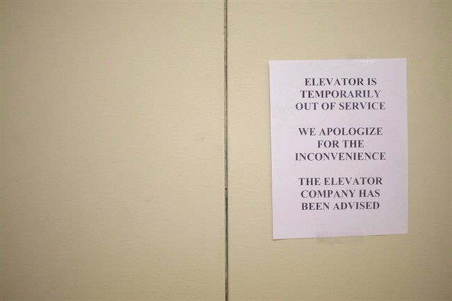 A sign is taped to a door of an elevator in a downtown Toronto office building on Wednesday, July 13, 2016. A retiree who says he hurt his leg after tumbling from a malfunctioning elevator in his downtown condominium is suing one of the world's largest elevator companies for negligence.