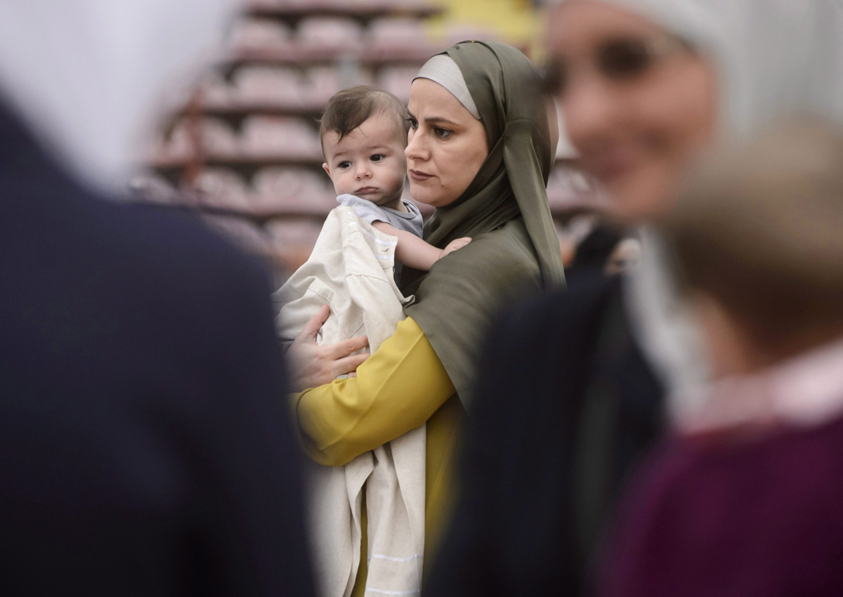 A Muslim woman holds a baby while taking part in Eid al-Fitr prayers in Bucharest, Romania, Tuesday, July 5, 2016.