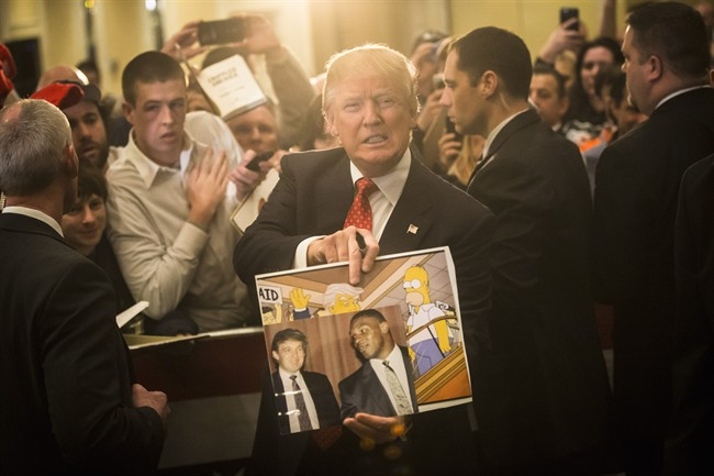 """In this Jan. 29, 2016, file photo, Republican presidential candidate Donald Trump holds depictions of himself on, """"The Simpsons"""" and a photo with boxer Mike Tyson, given to him by an attendee during a campaign stop at the Radisson Hotel in Nashua, N.H."""