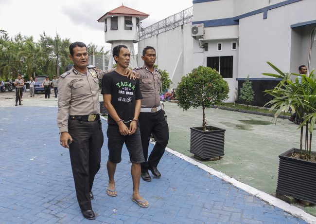 Police officers escort a captured inmate following a prison break at the Sialang Bungkuk Prison in Pekanbaru, Riau province, Indonesia, Saturday, May 6, 2017.