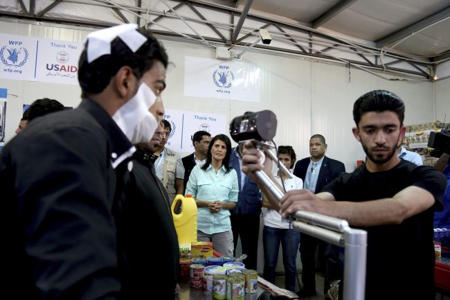 U.S. Ambassador to the United Nations Nikki Haley, background center, looks on as a bandaged Syrian refugee has his iris scanned at a supermarket, Sunday, May 21, 2017 in Zaatari Refugee Camp, Jordan.