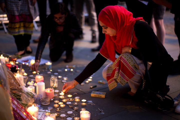 A woman lights candles after a vigil earlier this week in Albert Square, Manchester, England near the site of a suicide attack that left 22 people dead.