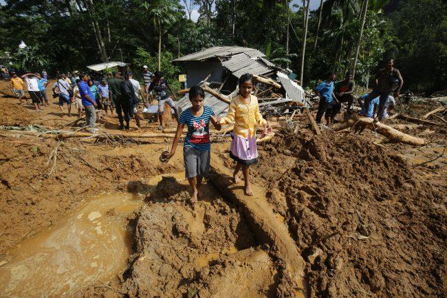 Children walk in mud where a landslide occured in at Athwelthote in Baduraliya, some 98 kilometers from Colombo, Sri Lanka, 28 May 2017.