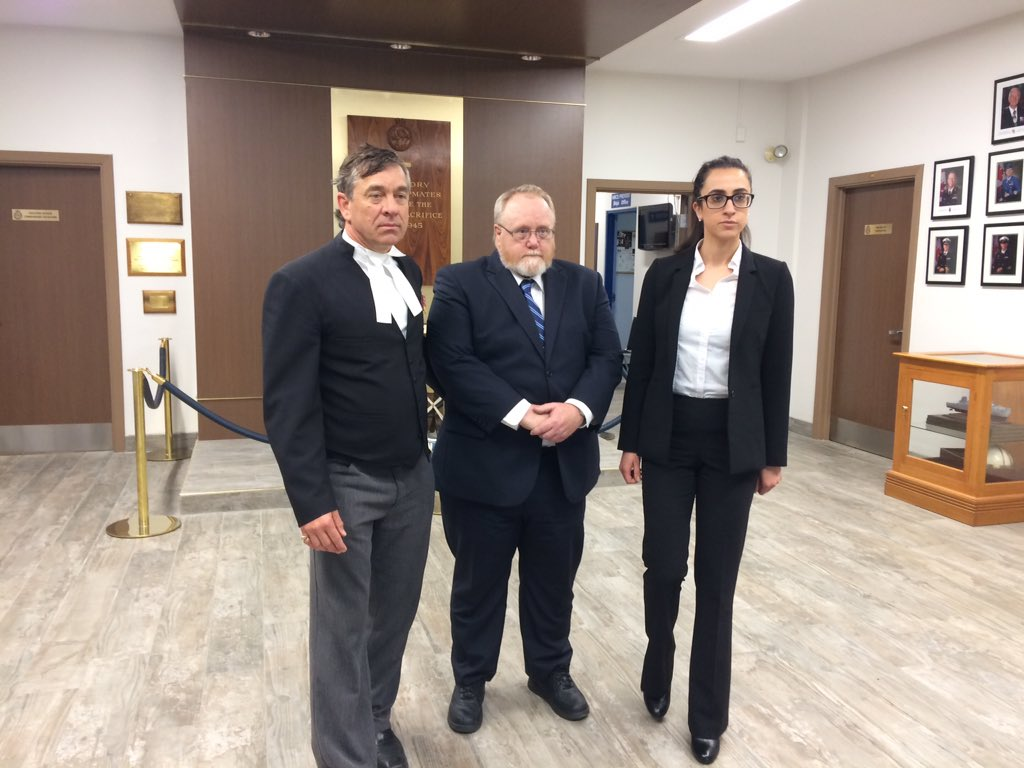 Former military medic James Wilks stands with his defence counsel at HMCS Prevost, London, on May 25, 2017.