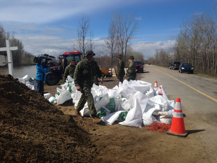 Soldiers with the Canadian Armed Forces fill sandbags in Yamachiche, Que., in order to reinforce temporary dikes on Tuesday, May 9, 2017. A state of emergency was declared in Yamachiche on Wednesday, May 10, 2017.