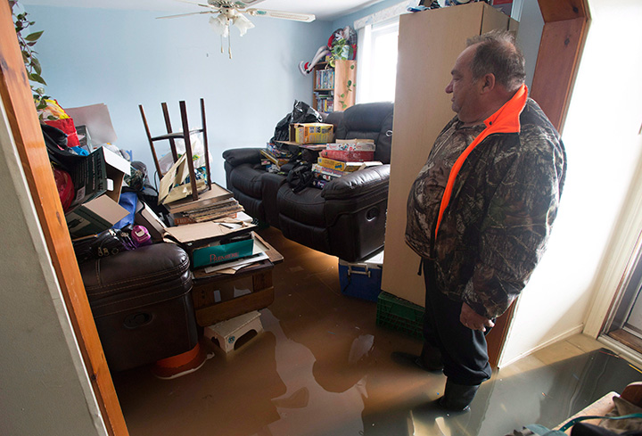 Flood waters lap at his feet as Marcel Theriault looks at his living room on the main floor of his home Sunday May 7, 2017 in Gatineau, Que.