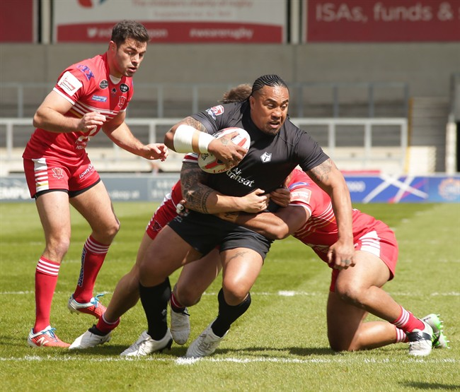 Toronto Wolfpack forward Fuifui Moimoi tries to break through a pair of tacklers in Toronto's 29-22 loss to the Salford Red Devils on April 23, 2017 in Salford, England, in the fifth round of the Ladbrokes Challenge Cup. THE CANADIAN PRESS/Toronto Wolfpack MANDATORY CREDIT.