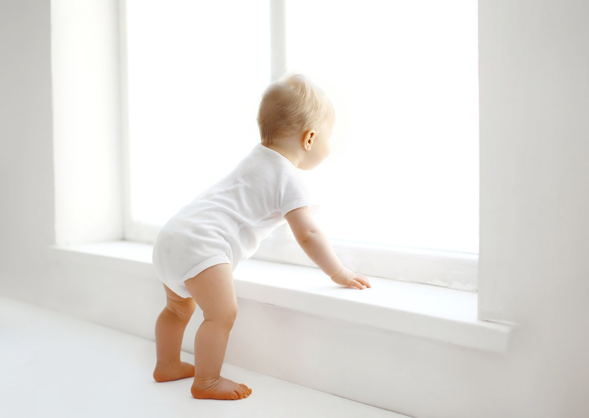 FILE: Baby stands near window.