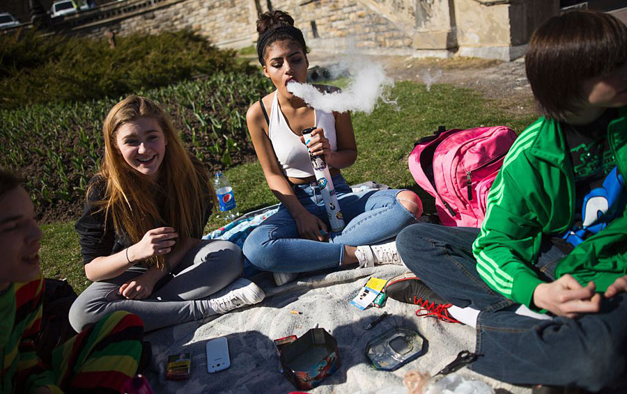 A woman blows smoke as another looks on as thousands gathered to celebrate National Marijuana Day in Ottawa on April 20, 2016.